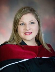 Photo of St. Paul's minister Rev. Sarah Grady in black graduation gown with red velvet stole.